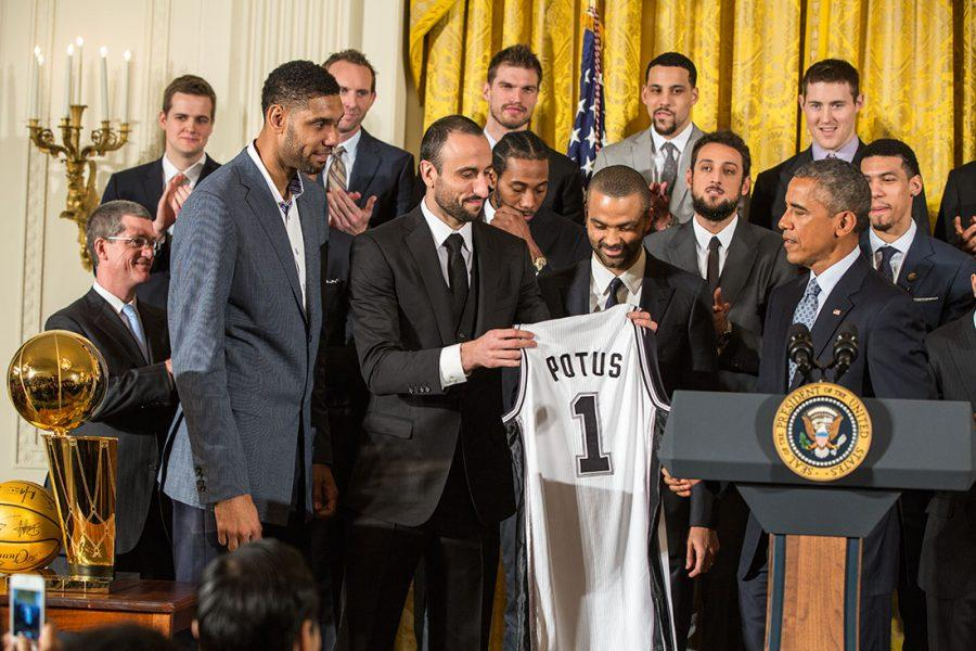 Tim Duncan, Manu Gin—bili and Tony Parker  present President Barack Obama with a Spurs team jersey during an event to welcome the 2014 NBA Champion San Antonio Spurs in the East Room of the White House, Jan. 12, 2015. (Official White House Photo by Pete Souza)